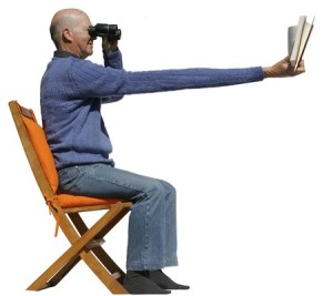 4559220 - short sighted man needs binoculars to read his book