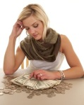 21269245 - a woman is sitting at a table full of money.