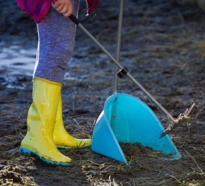 94237238 - girl collecting horse excrement in shovel at stableyard