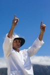 Low angle view of cricket umpire signalling six runs against blue sky