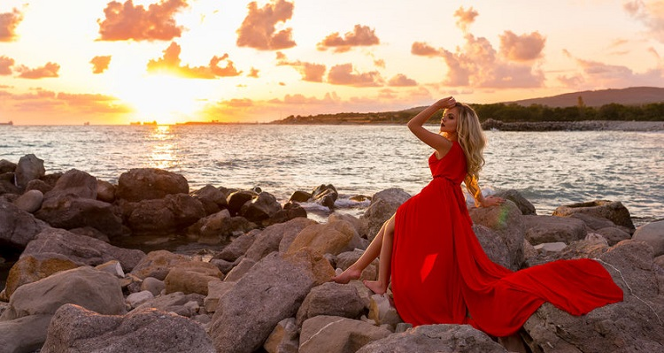 Young beautiful woman in red dress looking to blue sea and fiery sunset