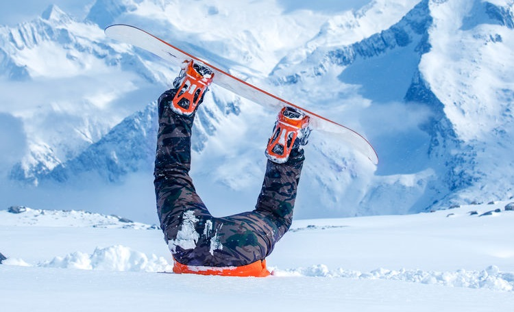 Legs of a snowboarder stuck in snow