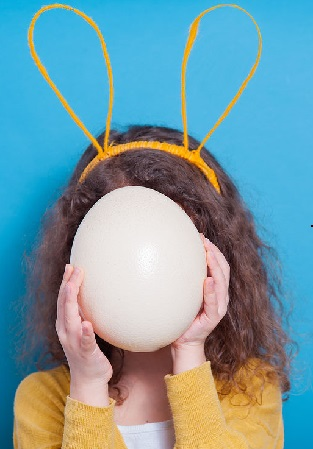 Girl with bunny ears with ostrich egg on a colored background.