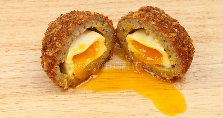 scotch-egg-runny-yolk-cut-half-wooden-board-52568825